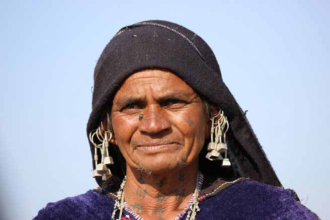 Rabari lady with tattoos on her face and traditional earrings